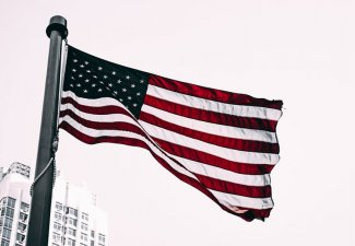 Photo of an American flag in front of a white building with a cloudy sky as a backdrop