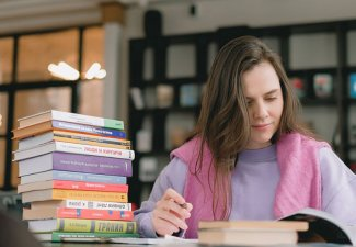 Photo of a person reading a book next to a stack of books