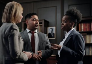 Photo of three people in formal wear conversating