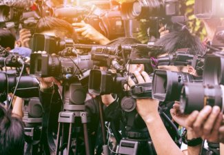 Photo of many news and media cameras pointed at the same target