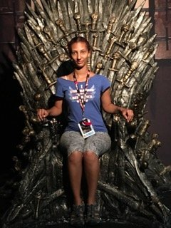 Doctoral student joan miller sits on the Iron Throne at Comic-Con International.