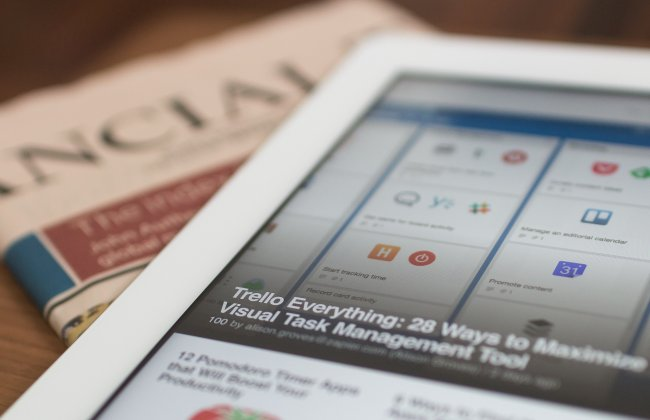 Photo of a tablet on top of a newspaper
