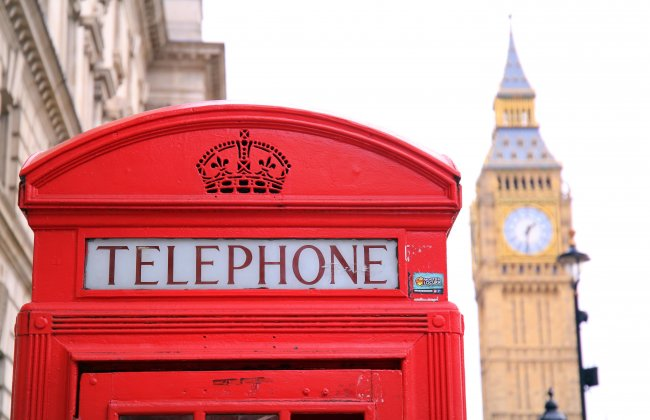Photo of a red telephone booth next to the Big Ben in London