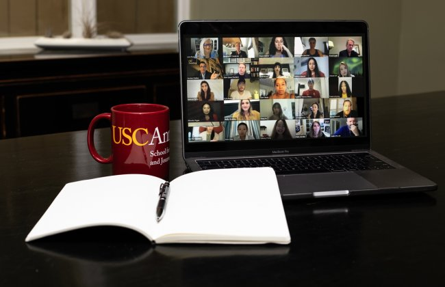 Photo of a USC Annenberg mug next to a zoom call on a computer and a notebook