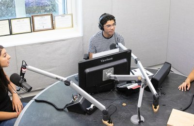 Photo of three people in a podcast studio