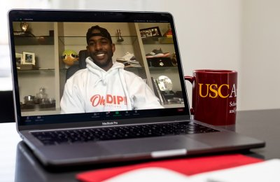 Photo of a person smiling in a video call and a USC Annenberg mug next to the computer