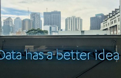 """Photo of a blue neon sign under a city window that reads """"data has a better idea"""""""