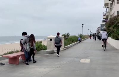 Photo of people walking on a beachfront walkway