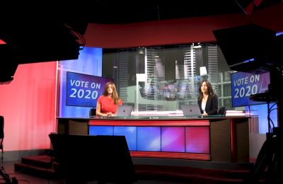 """Image of a news desk with televisions behind the hosts that read """"Election 2020"""""""
