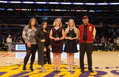 From let to right: Shannon Hearn, Kayla Hearn, Jodee Storm Sullivan, Keely Eure, and USC Annenberg School for Communication and Journalism Dean Ernest J. Wilson III, Ph.D., pose for a photo during the halftime of the Lakers - Hawks game. The Hearns and La