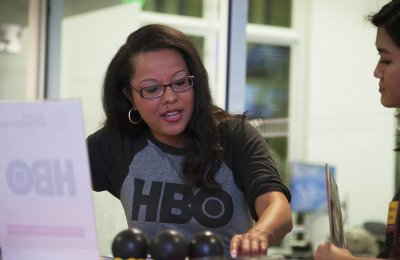 Photo of a person wearing an HBO shirt talking to another person