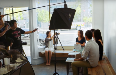 Screenshot from 'Mosaic: The China Dream' video depicting a film production crew around a group of people in a shop