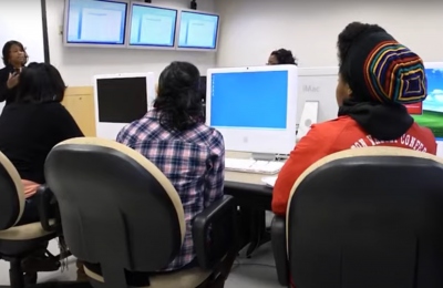 Screenshot from video of Alissa Richardson teaching to a group of people in a computer room