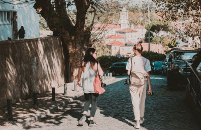 Photo of two travelling women walking down a street