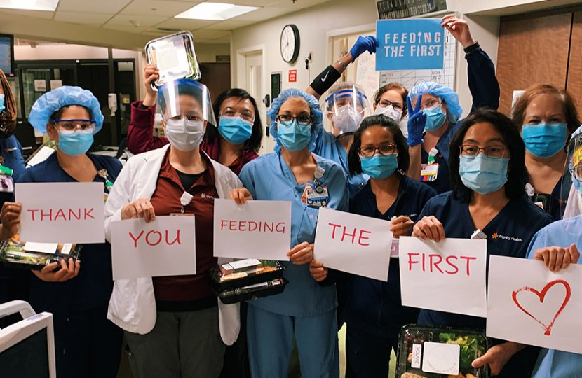 """Photo of medical staff holding signs that read """"thank you for feeding the first"""""""