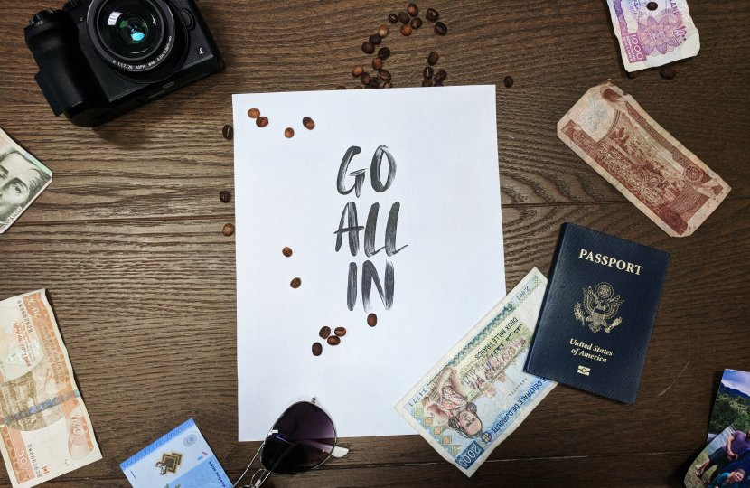 """Photo of a piece of paper that reads """"go all in"""" surrounded by sunglasses, a camera, a passport, and different money notes"""