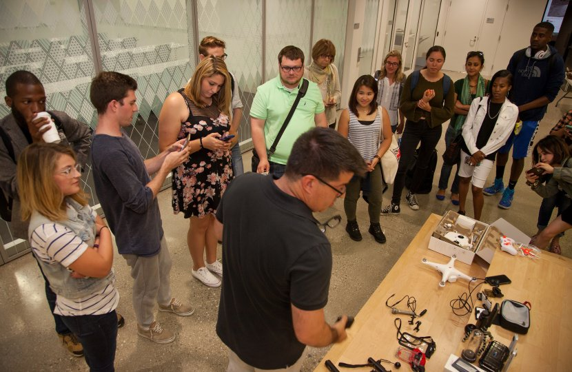 USC Annenberg professor Vince Gonzales (foreground, center) shows journalism graduate students an array of devices that enhance their phones for mobile journalism during the Summer Immersion boot camp. © USC Annenberg/Brett Van Ort