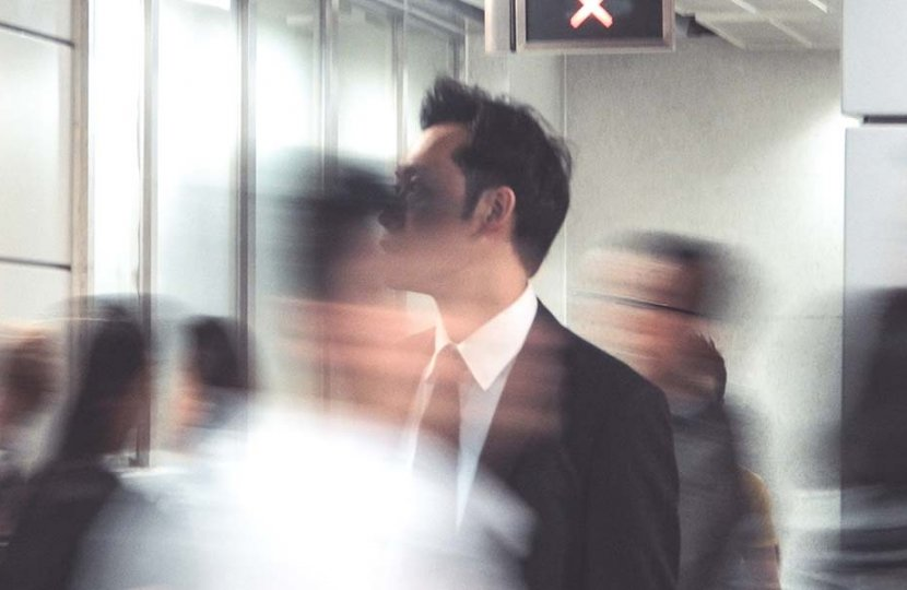 Photo of a person in business attire in focus with other people blurry around them