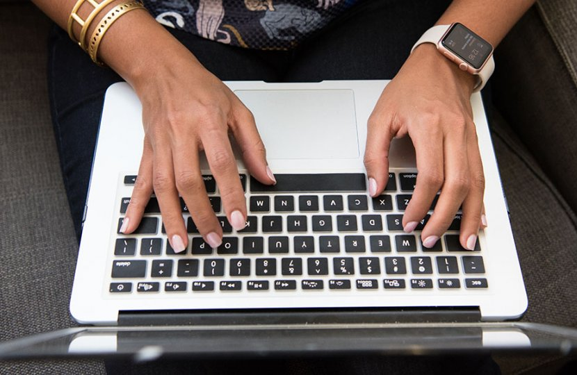 Photo of a person typing on a keyboard
