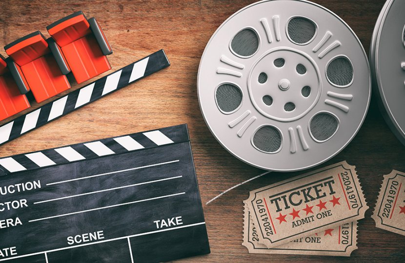 Photo of a film slate, film roll, and movie tickets