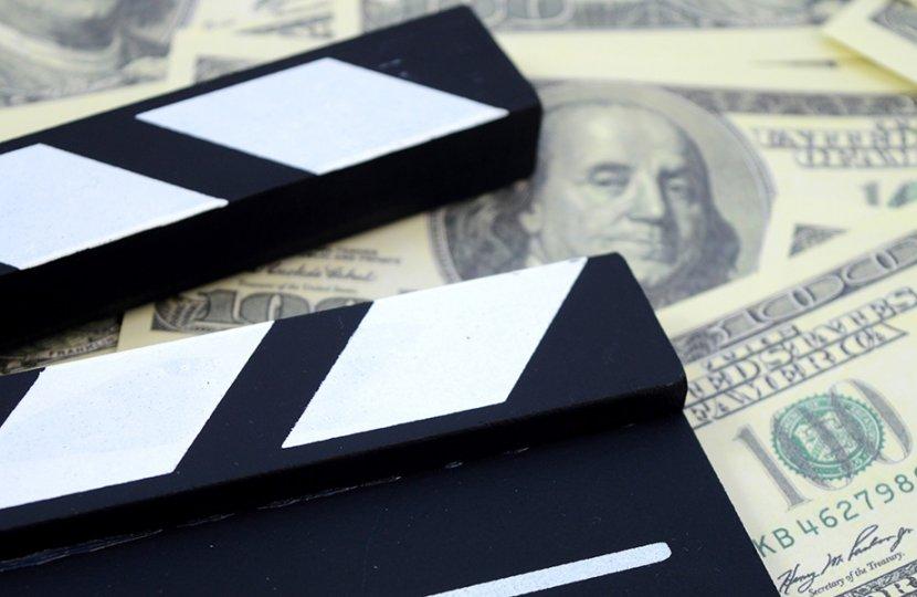 Photo of a slate over hundred dollar bills