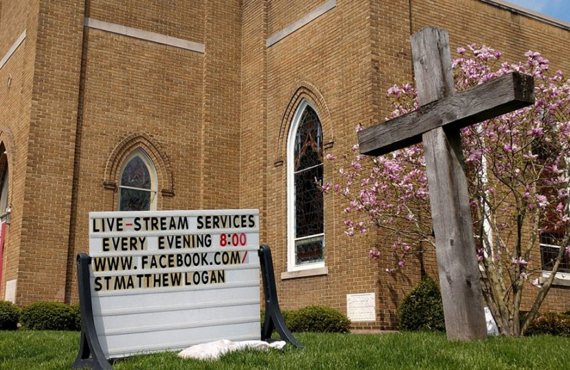 Photo of a worship center with a sign outside that promotes livestreamed remote worship practices