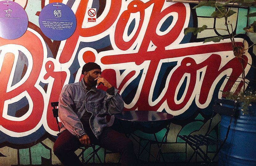 Photo of person sitting in front of Pop Brixton sign