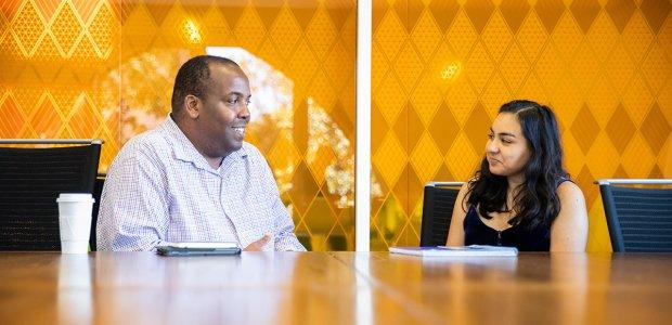 Photo of Jabari Brown advising a student