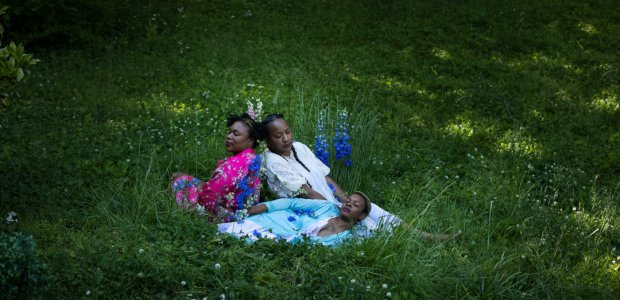 Three people laying in grass
