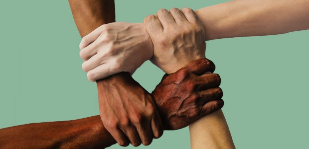 Four hands of different races grasp each other.