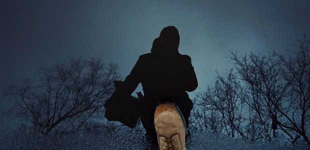Photo of a dark silhouette with a boot next to it and a cold dead winter landscape