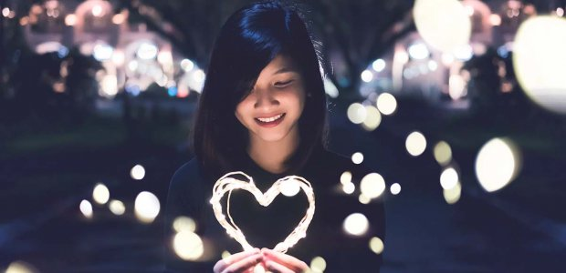 Image of a person surrounded by lights holding a heart made of light