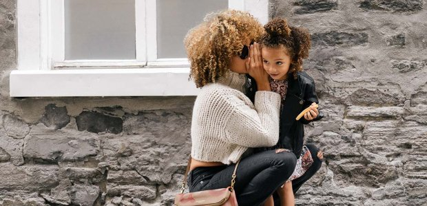 Photo of a person whispering into a child's ear