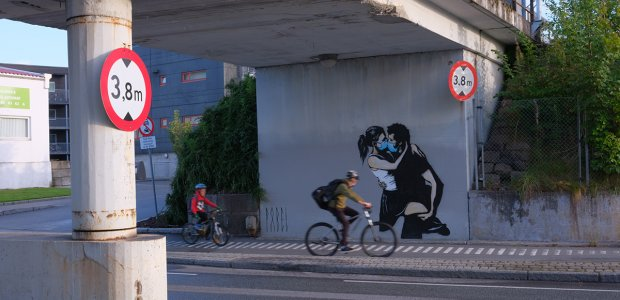 Two people on bicycles under a highway that has an illustration painted on of two people kissing with medical masks on