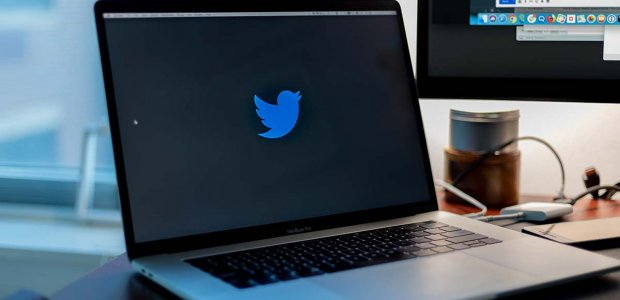 Photo of a laptop screen with the Twitter logo on it
