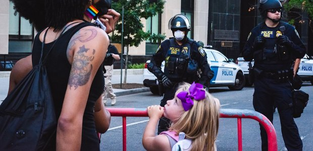 Photo of a protestor next to a small child in front of two police