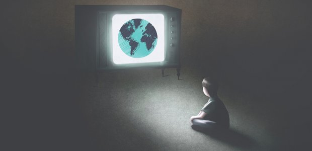 Image of person in a dark room watching a television that shows planet Earth