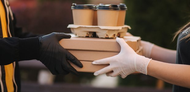 Photo of a person handing another a tray of coffee cups