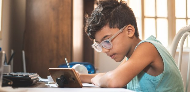 Photo of a child watching a phone and writing