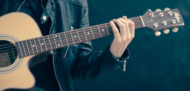 Photo of a person palying a guitar