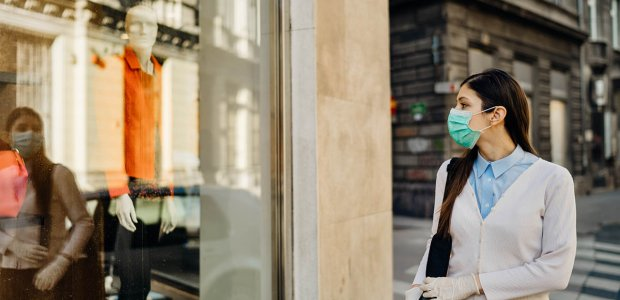 Photo of a person walking past a shop window and gazing at their reflection