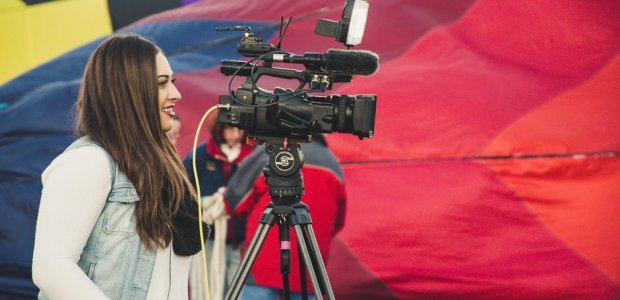 Photo of a person operating a news camera