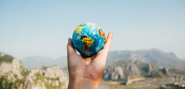 Photo of a person holding a small globe in their hands